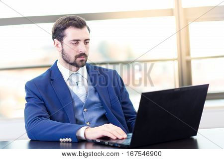 Portrait of successful corporate businessman in bright modern office focused on data on his laptop computer. Business and entrepreneurship concept.