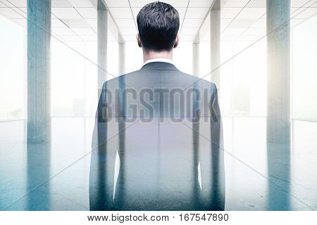 Back view of businessman in concrete room with bright daylight. Success concept. Double exposure