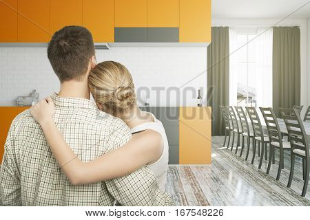 Back view of cuddling young european couple in modern kitchen interior. They are thinking about the future of their family