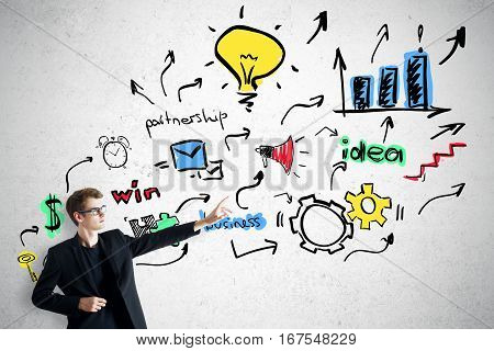 Young businessman insuit poiting at creative business sketch on concrete background. Targeting and success concept