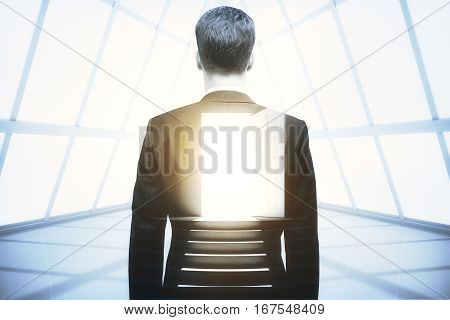 Back view of businessman in concrete room with open door. Opportunity concept. Double exposure