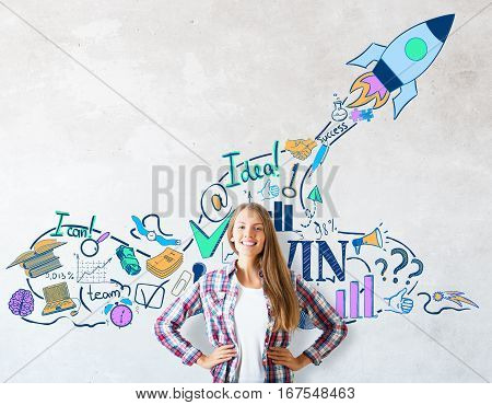 Smiling caucasian girl on concrete background with creative rocket ship sketch. Start up concept