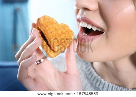 Young woman eating cookie, close up
