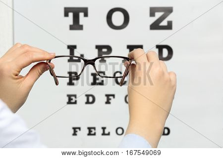 Young woman holding spectacles on eyesight test chart background, closeup
