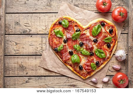 Pizza heart shaped love concept Valentine's Day romantic dinner food. Prosciutto, olives, tomatoes, parsley, basil and mozzarella cheese meal served on vintage wooden table
