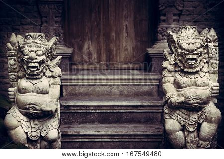 Ancient Asian demons deities at the enter to the old temple with old wooden door in vintage style