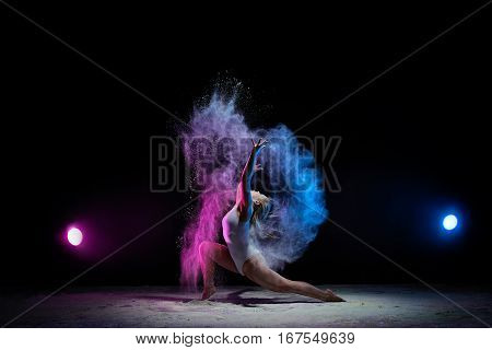 Female sexy gymnast in beige bodysuit bending gracefully with her hands up on black background with colored dust all over body shot made with color filters.