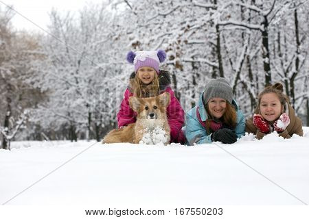 happy family - smiling mother and daughters with little cute corgi fluffy puppy at the winter day