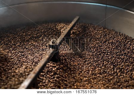 Machine for roasting coffee beans called roaster with a special automatic mixing device at work in a production room