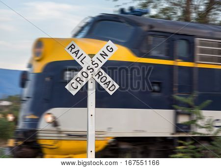 Sign for railroad crossing with Diesel locomotive engine speeding by on steep trip into mountains of West Virginia
