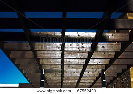 Wooden pergola for a blue and sunny sky