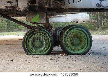 Old and rusty green plane landing wheels