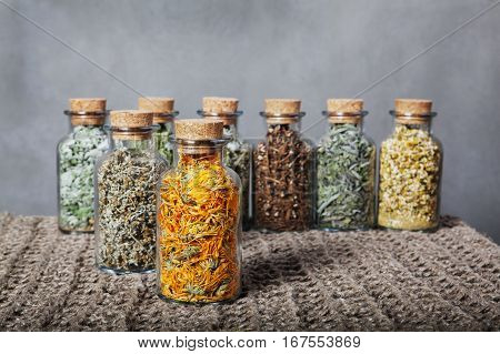 Different kinds of herbs. Dried, calendula, foreground Linen cloth