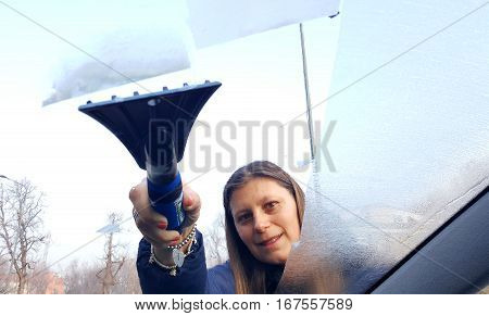 Woman scrapes away the ice from the windshield.