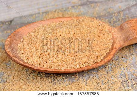Beige sugar in a spoon on wooden table