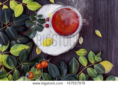 cup of hot tea on a wooden surface among the leaves top view