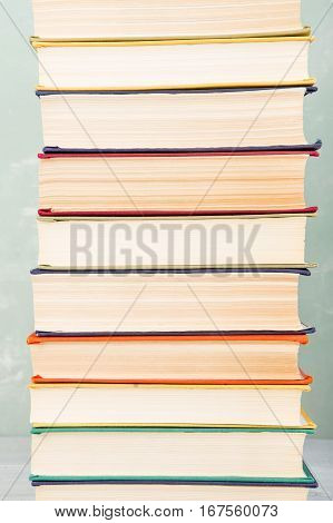 A Stack Of Old Colored Books On Shelf And Green Background