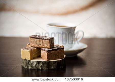 Homemade Sweets with Coffee on Wooden Coaster; Blurry Background