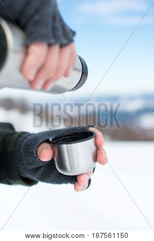 Man Using  Thermos In On A Snowy Mountain