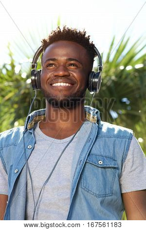Young Black Man Smiling With Headphones Outside