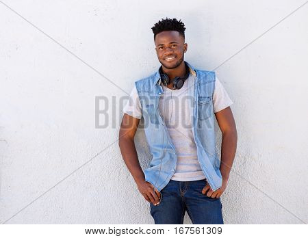 Smiling Man With Headphones Standing Against White Wall