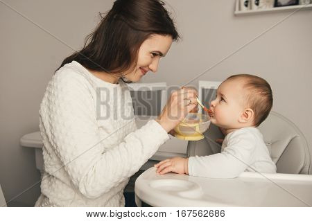 Mom feeding her baby girl with a spoon. Mother giving food to her eight-month child at home. Baby food.