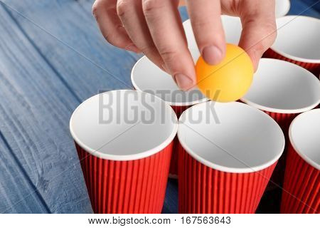 Yellow ball in male hand and paper cups arranged for playing beer pong