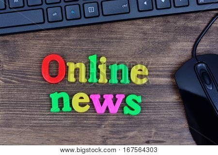 Online news words on wooden table closeup