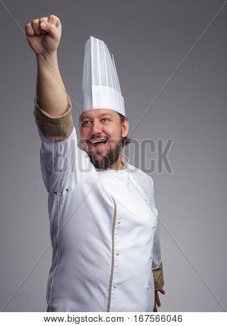 Bearded cook cap joyfully yells and pulls his hand forward