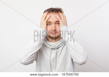 Man Looks Bewildered Forward, Clasping His Head With Hands