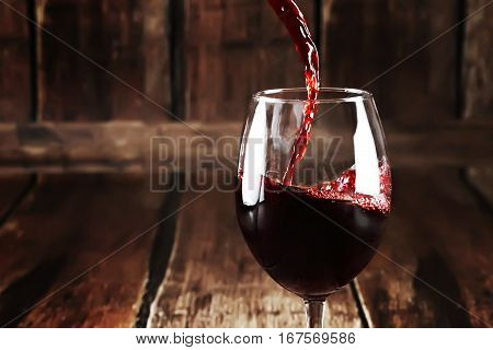 Closeup of glass with red wine on wooden background. Close up of pouring wine into transparent glass. Perfect alcoholic background. Macro of red wine in tall glass.