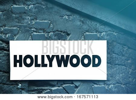 Street sign with word HOLLYWOOD on brick wall background