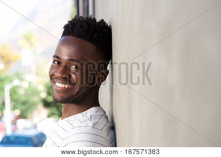 Side Portrait Smiling Man Leaning On Wall Outside