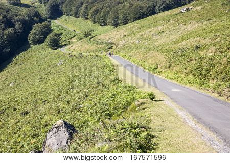 landscape with pilgrims walking a country road in the Pyrenees Atlantiques mountain in the French Basque Country, France