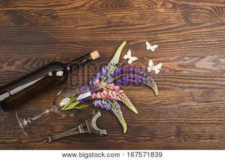 Bottle of wine and wineglass with puffy violet lupins on the wooden background