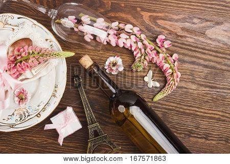 Tableware and silverware with puffy light pink lupins on the wooden background