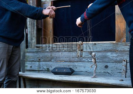 Puppeteer holding a marionette skeleton and coffin. Halloween puppet show.
