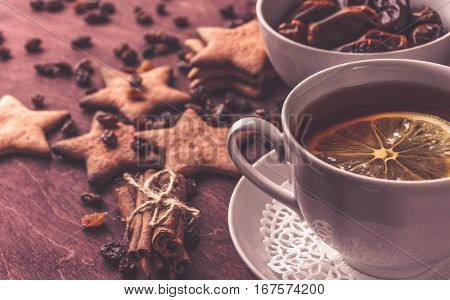 Cup of tea with lemon and handmade ginger cookies and cinnamon at background on red wooden table. Morning breakfast