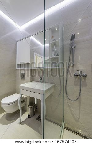 Modern en-suite bathroom with shower cabin in apartment