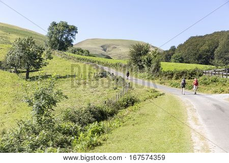landscape with pilgrims walking a country road in the Pyrénées Atlantiques mountain in the French Basque Country, France