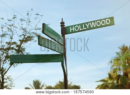 Street sign with word HOLLYWOOD on sky background