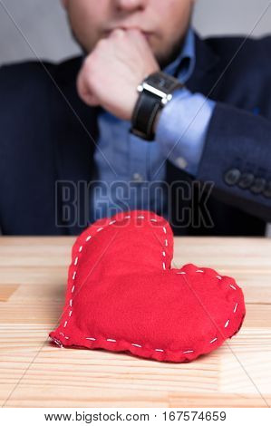 Elegant man in a suit with homemade red heart on Valentine's Day. Natural wooden table.