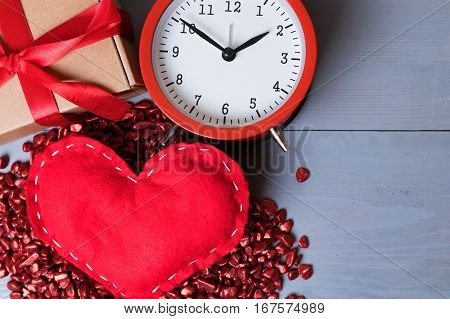 Red homemade heart with present or gift and a vintage clock on Valentine's Day. Copy space on the right. Time for love or romance abstract concept.
