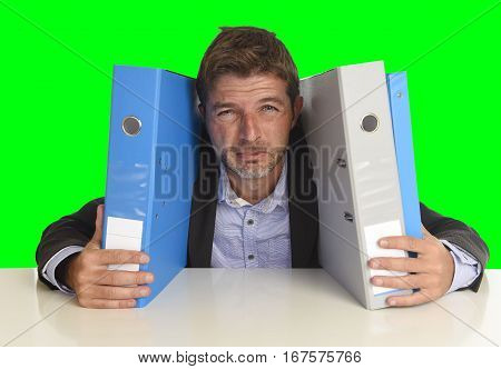 young attractive busy businessman overwhelmed suffering crazy stress at office exhausted holding paperwork folders tired crying on desk isolated on green chroma key screen background