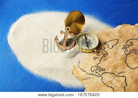 Compass, anchor and old map in sand on blue background. Columbus Day concept