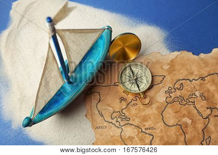 Wooden boat, compass and old map on blue background. Columbus Day concept