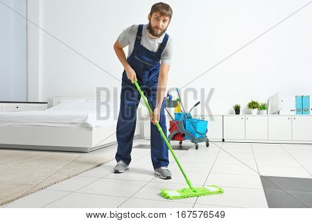 Funny young man moping floor at home