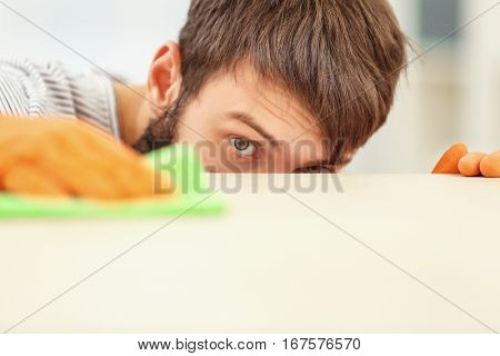 Bearded young man wiping furniture with napkin, close up