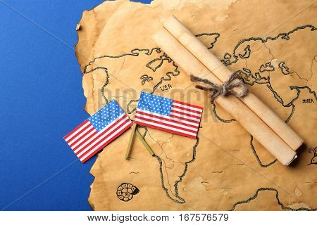 USA flags, scroll and old map on blue background. Columbus Day concept