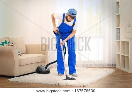Young man hoovering carpet with vacuum cleaner at home